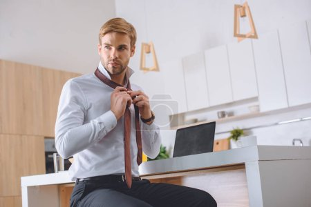 Photo for Confident young businessman tying necktie at kitchen table with laptop - Royalty Free Image
