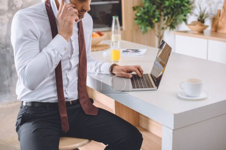 cropped image of businessman in white shirt with necktie over neck talking on smartphone and working on laptop at kitchen