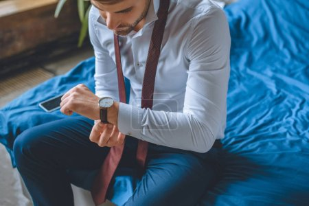Photo for Selective focus of businessman in white shirt and necktie over neck putting on wristwatch in bedroom at home - Royalty Free Image