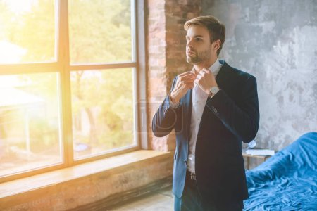 young businessman adjusting collar of white shirt in bedroom with sunlight from windows