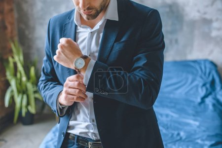 Photo for Cropped image of businessman in suit putting on wristwatch in bedroom at home - Royalty Free Image