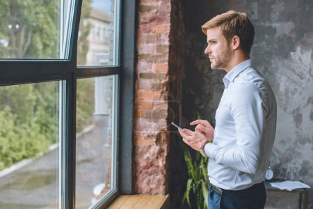 thoughtful young businessman with smartphone standing in living room at home