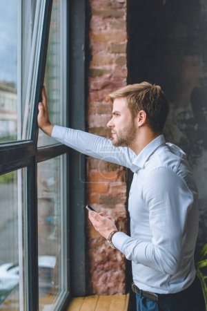 pensive young businessman with smartphone looking in windows at home