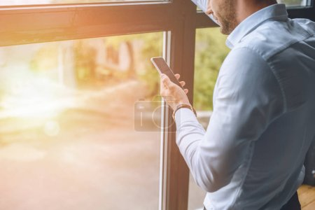 Photo for Cropped image of young businessman using smartphone near windows with sunlight - Royalty Free Image