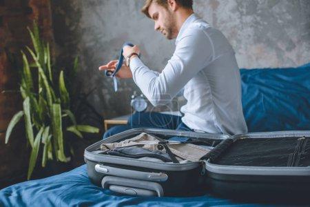 Photo pour Foyer sélectif de l'homme d'affaires emballage des bagages dans la valise dans la chambre à coucher à la maison - image libre de droit