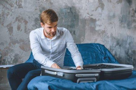 Photo pour Homme d'affaires sérieux emballant les bagages dans la valise dans la chambre à coucher à la maison - image libre de droit