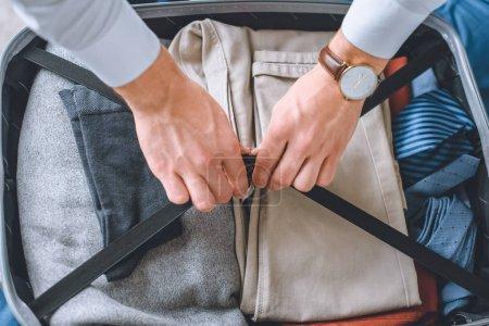 Photo pour Image recadrée de l'homme d'affaires avec montre-bracelet emballage bagages dans la valise - image libre de droit