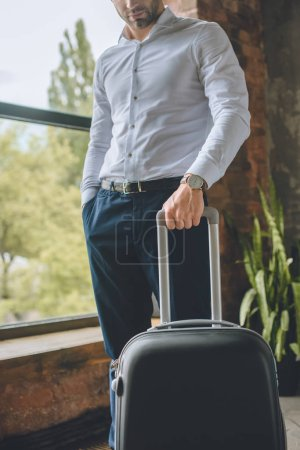 cropped image of male tourist standing with suitcase at home