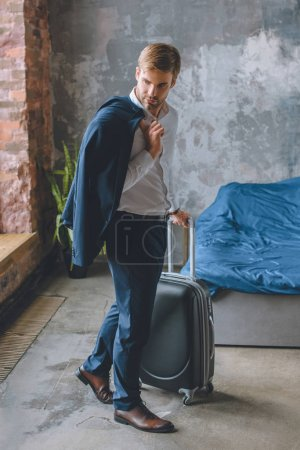 young businessman with jacket over shoulder carrying suitcase in bedroom at home