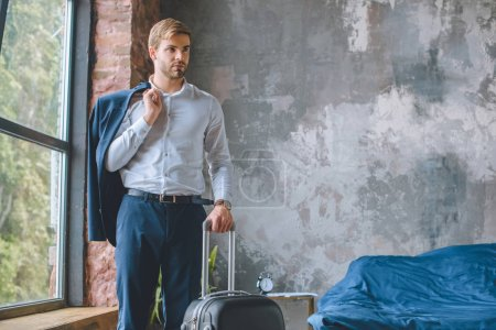 Photo for Confident male traveler with jacket over shoulder standing with suitcase in bedroom at home - Royalty Free Image