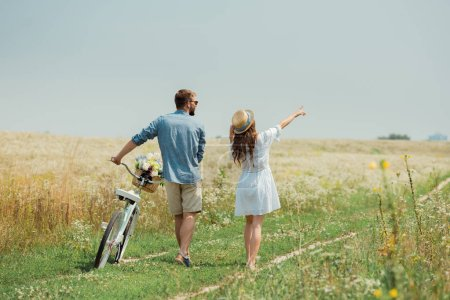back view of couple with retro bicycle in summer field with wild flowers