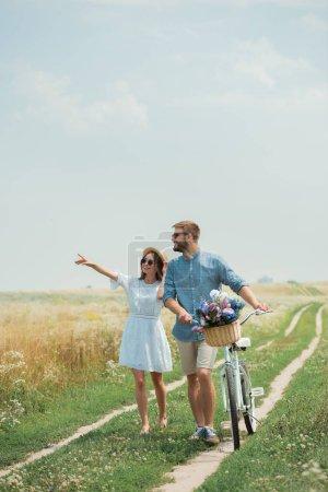 Lächelndes Paar mit Sonnenbrille und Retro-Fahrrad im Sommerfeld mit Wildblumen