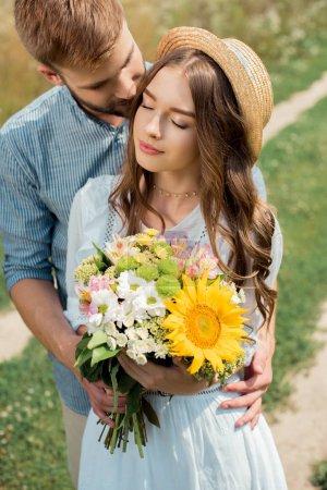 tender man hugging girlfriend with bouquet of wild flowers in summer field