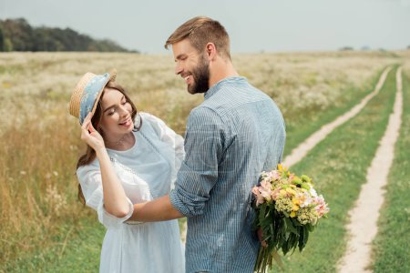 smiling man hiding bouquet of wild flowers for girlfriend behind back in summer field