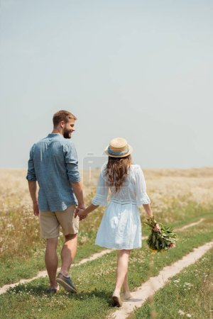 back view of woman in white dress with bouquet of wild flowers walking together with boyfriend in field