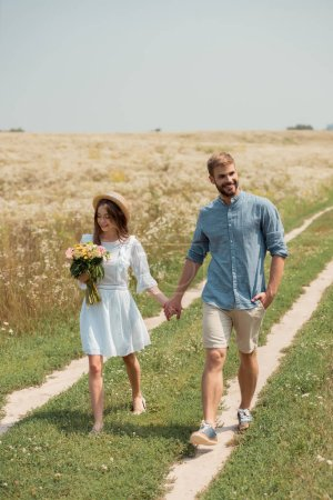 woman in white dress with bouquet of wild flowers walking together with boyfriend in field