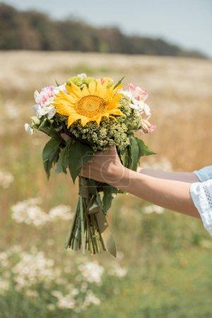 Photo pour Plan recadré de femme tenant bouquet de fleurs sauvages dans le champ - image libre de droit