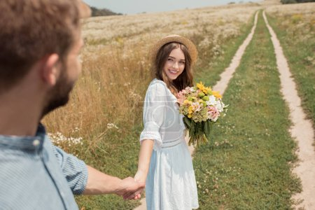 partial view of smiling woman with bouquet of wild flowers and boyfriend holding hands in field