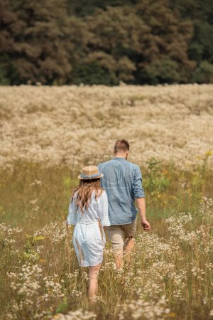 rear view of couple walking in filed with wild flowers around
