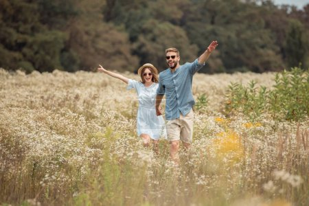 Photo for Happy lovers holding hands while running in field with wild flowers - Royalty Free Image