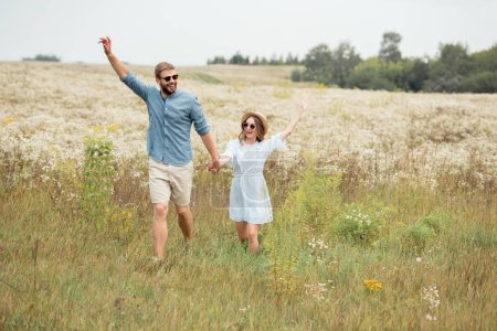 happy lovers holding hands while running in meadow with wild flowers