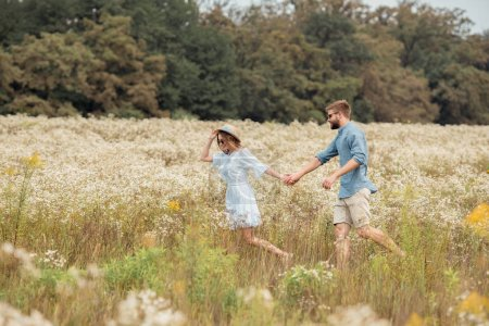 side view of young lovers holding hands while walking together in field with wild flowers