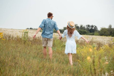 back view of young lovers holding hands while running in field with wild flowers
