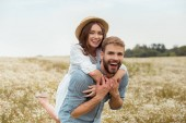 happy lovers piggybacking together in meadow with wild flowers