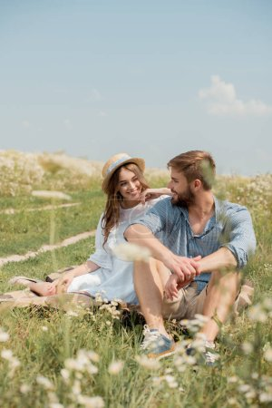 cheerful young lovers sitting on blanket in field with wild flowers on summer day