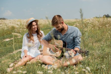 man playing acoustic guitar to smiling girlfriend in summer filed