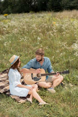 man playing acoustic guitar to girlfriend in summer filed