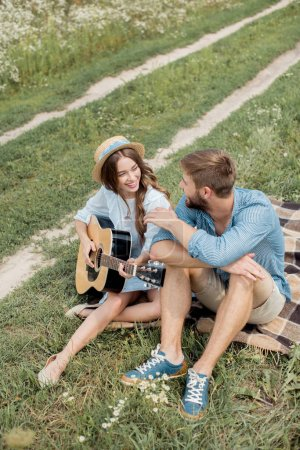 smiling woman playing acoustic guitar to boyfriend in summer filed