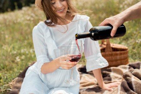 Photo pour Vue partielle du vin rouge battante homme dans copines verre dans le champ - image libre de droit