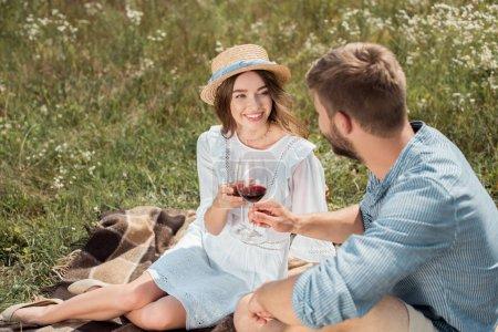 Photo pour Couple souriant cliquetis verres de vin rouge dans le champ d'été - image libre de droit