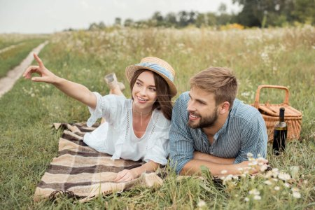 smiling woman showing something to boyfriend while resting on blanket together in summer field