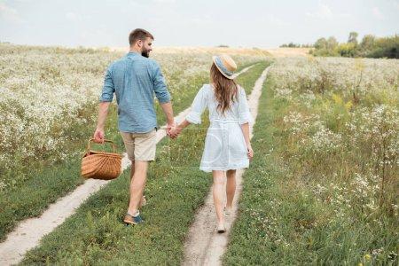 vue arrière du couple avec panier pique-nique, main dans la main tout en marchant dans le champ
