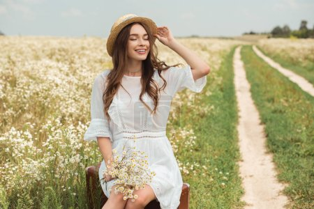 smiling woman in white dress with bouquet of wild camomile flowers sitting on retro suitcase in field
