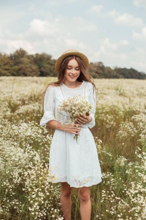portrait of pretty woman in white dress with bouquet of wild camomile flowers on meadow