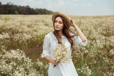 Photo pour Portrait de jolie femme chevaleresque en robe blanche avec bouquet de fleurs de camomille sauvage sur prairie - image libre de droit