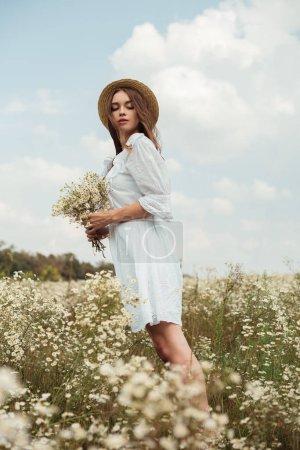 Foto de Mujer bonita en vestido blanco con ramo de flores de manzanilla silvestre en Prado - Imagen libre de derechos