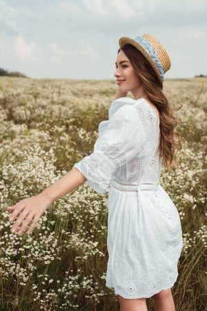 pretty woman in straw hat and white dress on meadow with wild flowers
