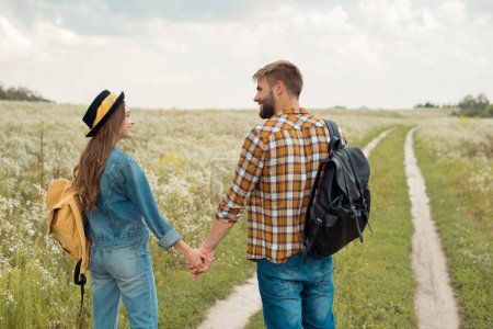 rear view of happy lovers with backpacks holding hands in field with wild flowers