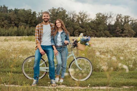 young lovers with retro bicycle in field with wild flowers