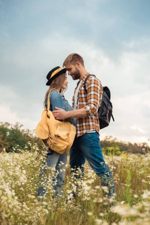 tender couple in love with backpacks in summer field with wild flowers