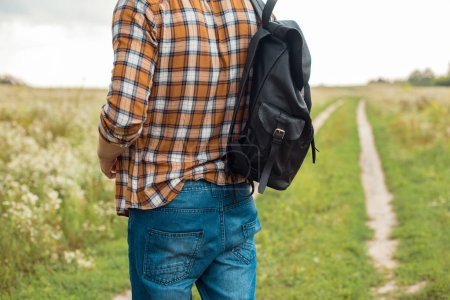 partial view of man in jeans with black leather backpack standing in field