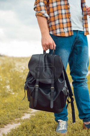 partial view of man in jeans holding black leather backpack in field
