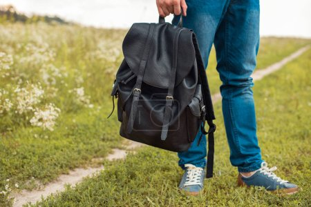 Photo for Partial view of man in jeans holding black leather backpack in field - Royalty Free Image
