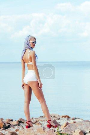 elegant woman posing in white retro swimwear and silk scarf on rocky shore near sea