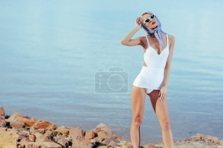 attractive stylish girl posing in white vintage swimsuit, sunglasses and silk scarf on rocky shore