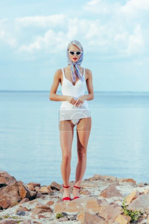 stylish girl posing in white vintage swimsuit, trendy sunglasses and silk scarf on shore